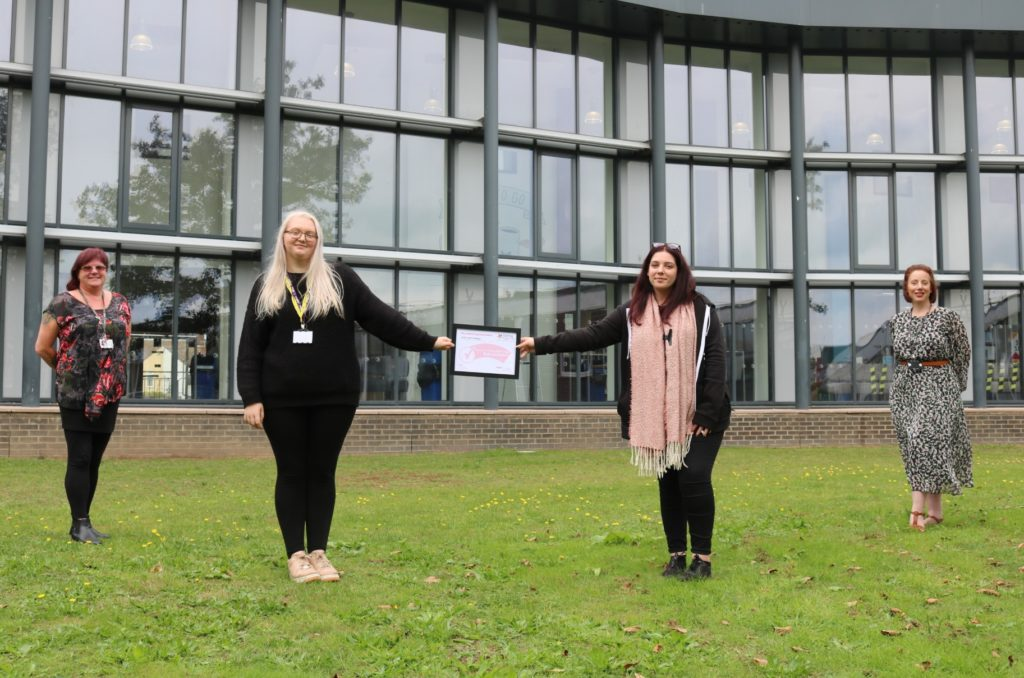 Maria Watson, Student Wellbeing and Tutorial Co-ordinator, East Coast College student ambassadors Chelsea Tomkinson and Chloe Eden and Catherine Duffield, Student Services Manager, holding the Carer Friendly Tick Award outside the college.